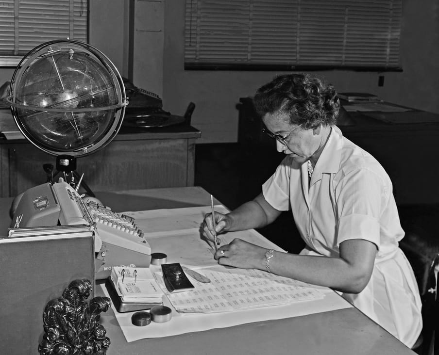 Black and white photograph of a woman with glasses sitting at a desk, working.