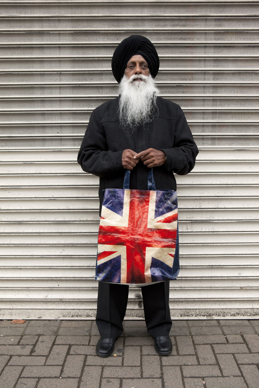 Photo of a Sikh man standing with a bag in his hands, showing the UK flag