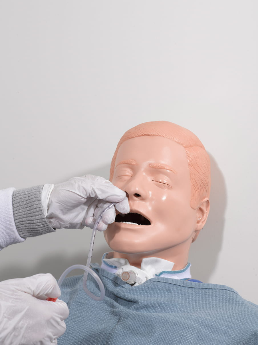 The head of a peach-coloured male mannequin with short hair, eyes closed, is leaned against a white wall, with its mouth open as white gloved hands insert a plastic tube into its left nostril