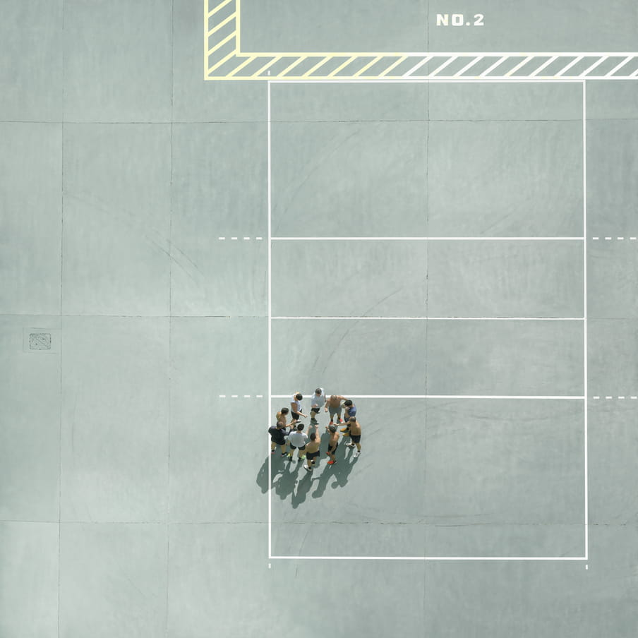 Photograph taken from above on a mint green court showing a group of men gathered in a circle.
