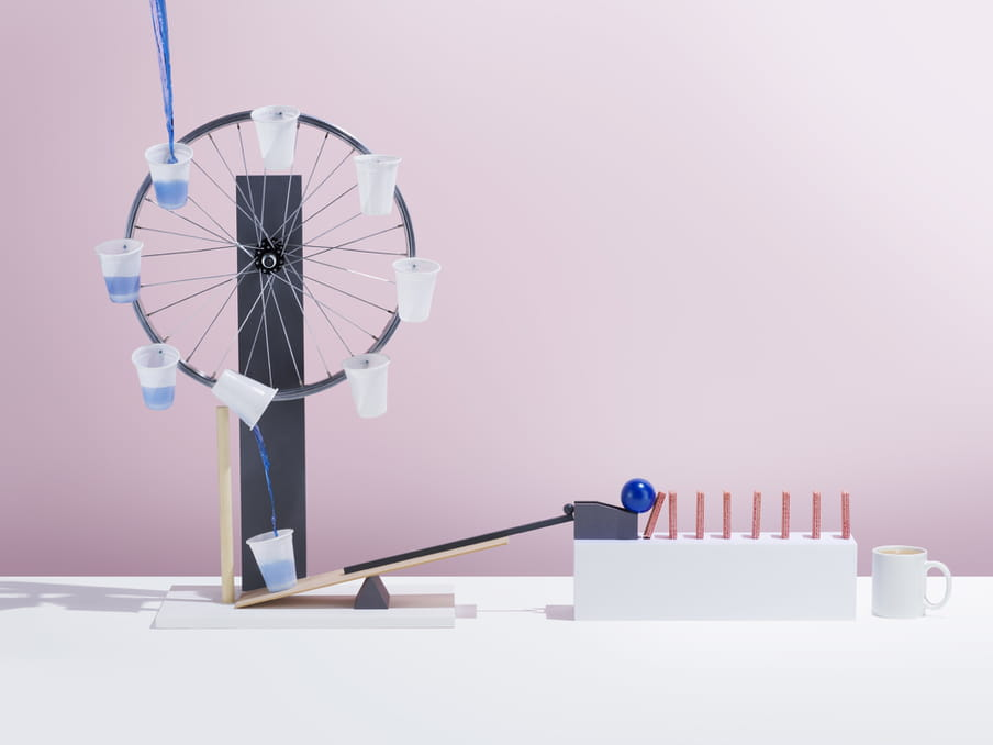 Blue water is poured into one of many rotating white plastic cups attached to a wheel, which pour back down into a cup. This ever filling cup is on a wooden platform connected to a blue ball which rolls onto a stack of pink domino style sticks of sugar. A white mug of brown liquid awaits on the right, for the sugar stick to fall into it. The background is pink.