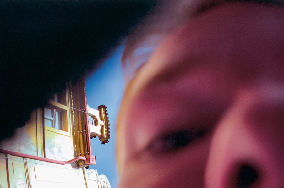 A close up photo of the nose and eye of a man, out of focus, outside with a building in the background.