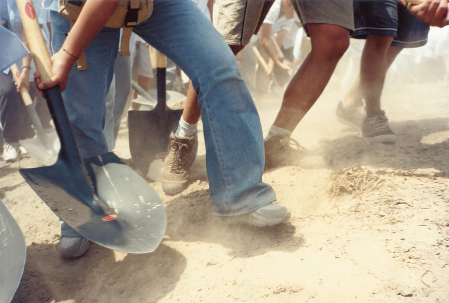 Dusty desert floor, legs in jeans and black trainers pictured holding a shovel, with more legs and shorts in background