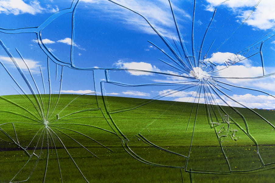 Photograph showing a broken glass in front of a green land and a blue sky.