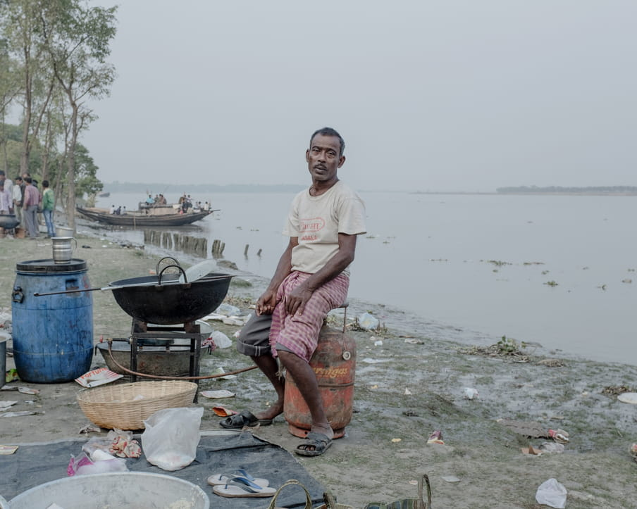 Colour photograph of a man sitting on gaz tank, his back to the water, while looking at the camera. He is wearing a beige t-shirt with something red written on it, grey bermuda pants covered with a piece of pink checked fabric and sandals coming off of his feet. He sits in front a a huge cocking pot. Around him on the muddy ground, are some plastic waste. A group of men are standing in the distance and a boat is floating near the shore.