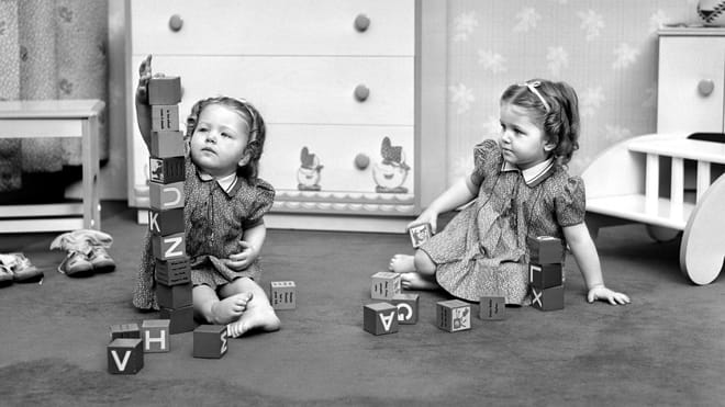 Old black and white photo of two little girls sitting on the floor and playing with wooden blocks with letters on them. The left kid has built a high tower out of the blocks, the right one is looking at it while holding a block.