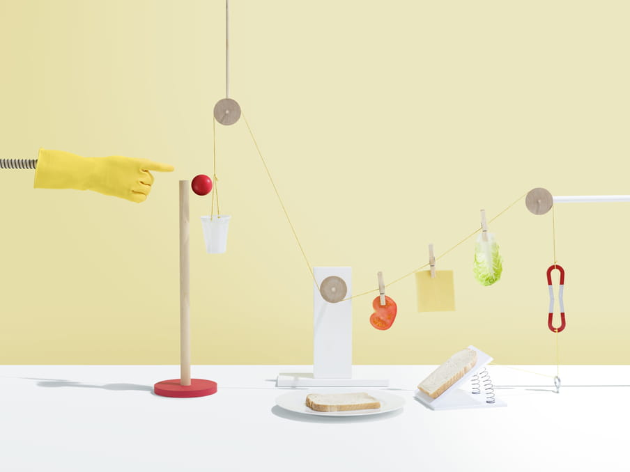 Pieces of salad, cheese and tomato are held onto a string by wooden pegs connected to three circular wooden objects. To the left, a yellow rubber glove on a metal pole seems to have just pushed a red ball off a wooden pole on a stand, and into a white plastic cup. Two pieces of bread lie on a plate and on a stand supported by metal strings.