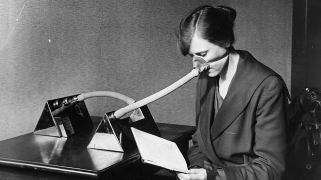 Black and white photograph of a woman reading while wearing a breathing mask on her nose.