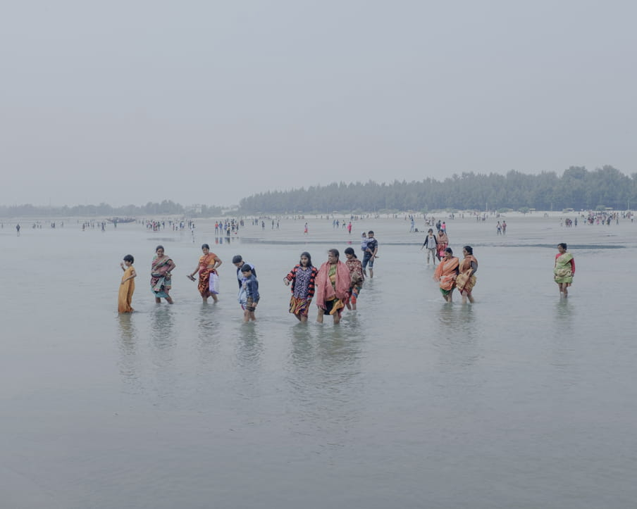 A group of people are walking alone or two by two, holding arms, in the water, pulling their colourful clothes up to their knees. A women is holding her shoes and a bag, a man in the background is carrying a child. We can see the beach and some greenery in the distance with other people standing around.