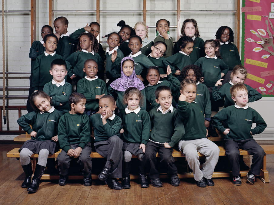 A school photograph of a set of four rows of young happy children posing on benches, with seven at the front, six in the row up, seven in the row behind and eight at the top. They are pulling poses such as with their hands on their hips, posing with chin in hand, pretending to be strong with a fist up at an angle, waving or standing close to another child. The floor is wooden and there is a gymnastic structure behind them, with a children-made poster to the right, in pink. The children wear green jumpers.