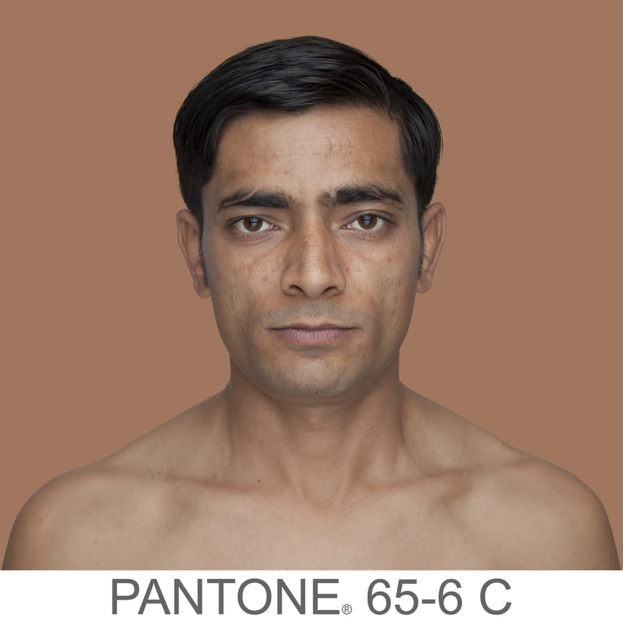 Photographic portrait of a male with short hair and no beard. The background is a sample of 11 x 11 pixels taken from the nose of the subject and matched with the industrial pallet Pantone®. The pantone color is written out as PANTONE 65-6 C.