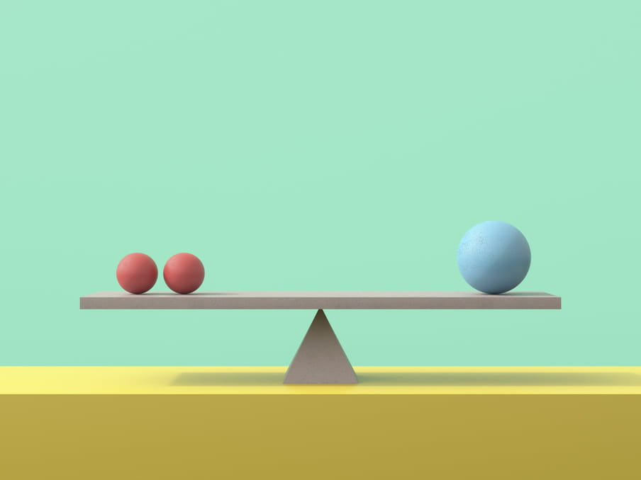 Image against a light green background illustrating a balance, formed of a 3D triangle on a bright yellow shelf, holding a grey plank which has two smaller red balls on one side and one larger blue ball on the other side. The shadow of the plank lies across the yellow shelf below.