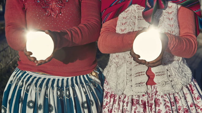 Photo of two humans holding in their hands two mirrors and reflecting the light with them