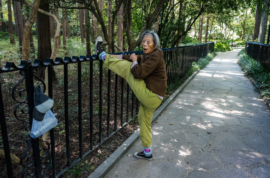 A older person in lime grey jogging pants, a brown top and trainers and pink and blue socks, stretching her leg up high ahainst against a black iron park railing, her hands reaching out to keep the foot up. Their plastic bag with a thermos in and a black and white cap also hang on the railing. The path is lit with sun through the trees