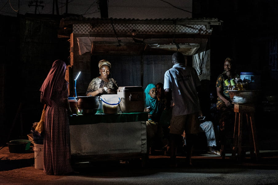 Photograph taken at night with people gathered behind a small stand lit by a precarious lamp. On the left side of the frame, big jars and containers lay on the counter.