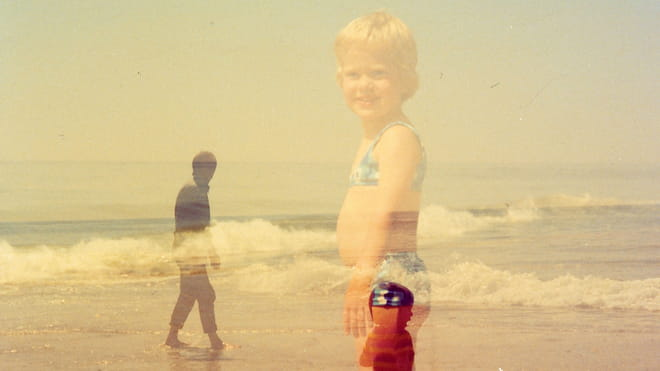 Photo of two kids and a grown man on the beach with waves in the sea on the background. Due to double exposure the opacity of everything is not 100%.