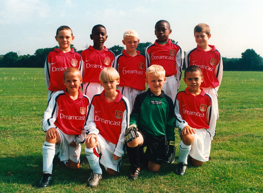 Photo of the Arsenal Advanced team of 2001 taken on a sunny day. A team of 9 boys in total on the green grass of a pitch; 5 standing in the back row and 4 half kneeling in front. Jamie Lawrence is the boy standing in the back right. Harry Kane is bottom left, kneeling.