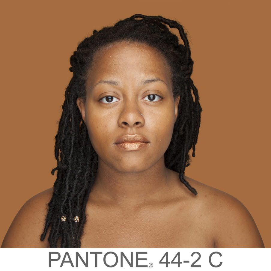 Photographic portrait of a woman with braids and a nose piercing. The background is a sample of 11 x 11 pixels taken from the nose of the subject and matched with the industrial pallet Pantone®. The pantone color is written out as PANTONE 44-2C.