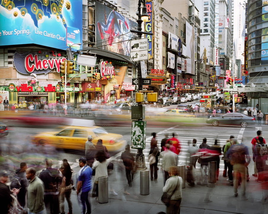 Photo of a busy street with a road trough it, yellow cabs and other cars on it. Many buildings in the back, commercials hanging all over it. It's shot with a high shutter speed, so people are blurred