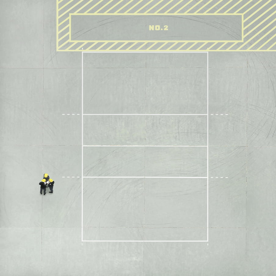 Photograph taken from above of three men with yellow hats gathered in a circle on a mint green court.
