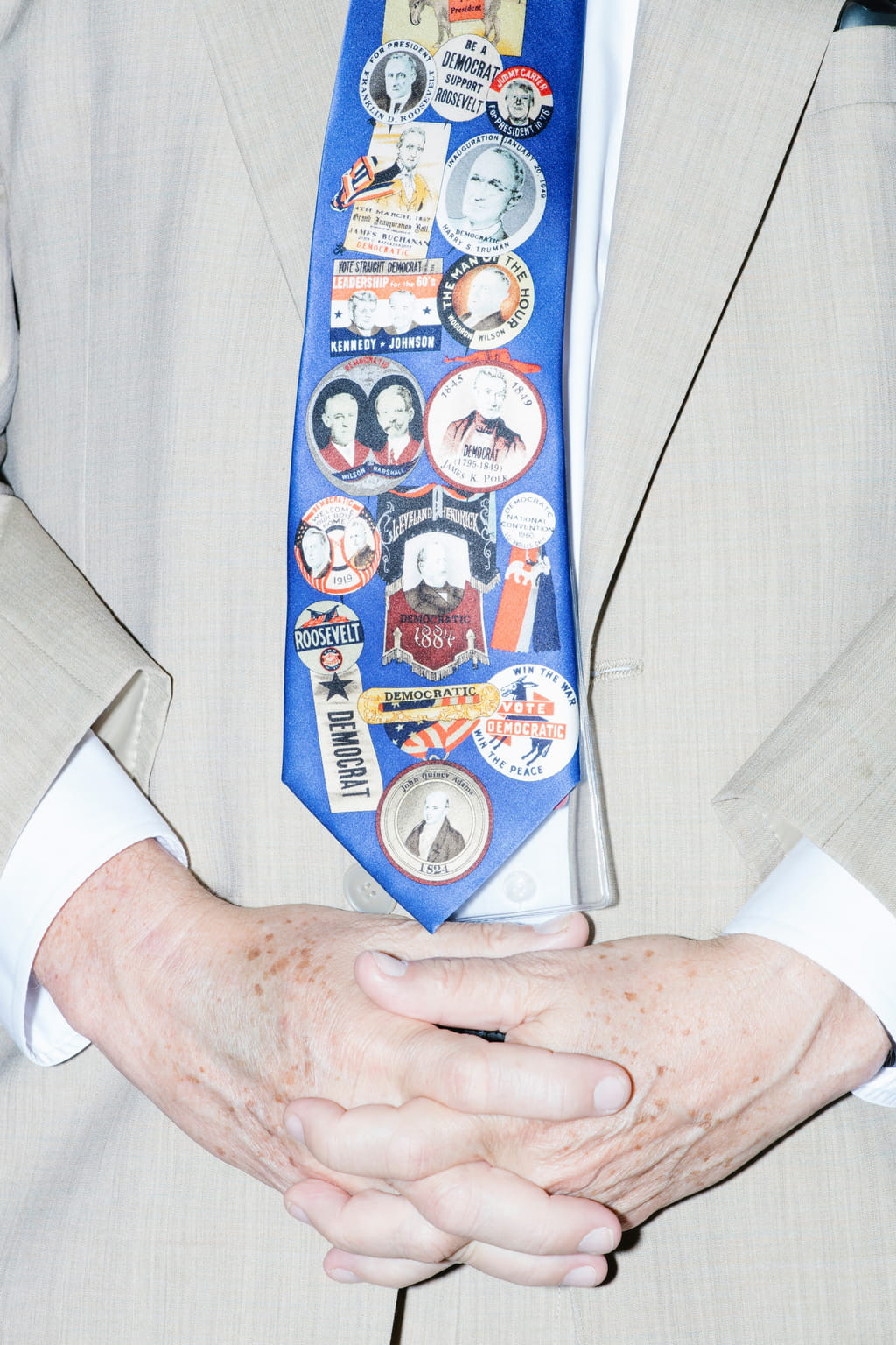 Close-up of folded older looking hands against a pale cream suit, wearing a blue tie covered in political stickers, saying such things as 'Roosevelt Democrat' or 'Kennedy-Johnson'