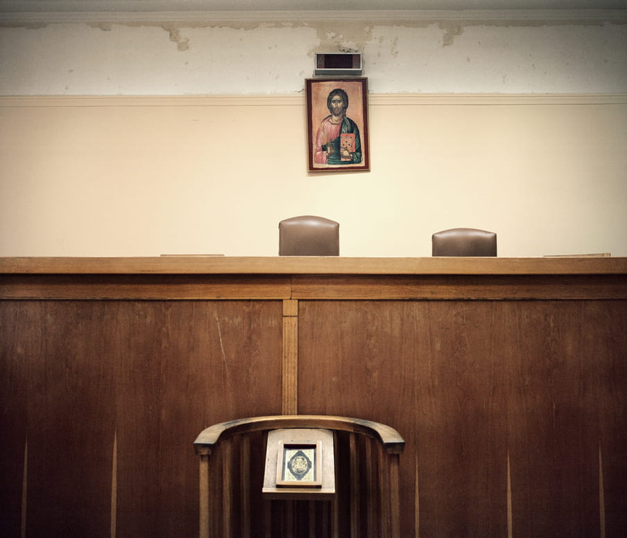 A stand before an empty courtroom, which badly needs a coat of paint, with an artistic religious portrait  on the wall.