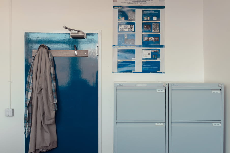 Office with two filing cabinets, a door with a coat hanging on it and a poster with brain graphics on the wall.