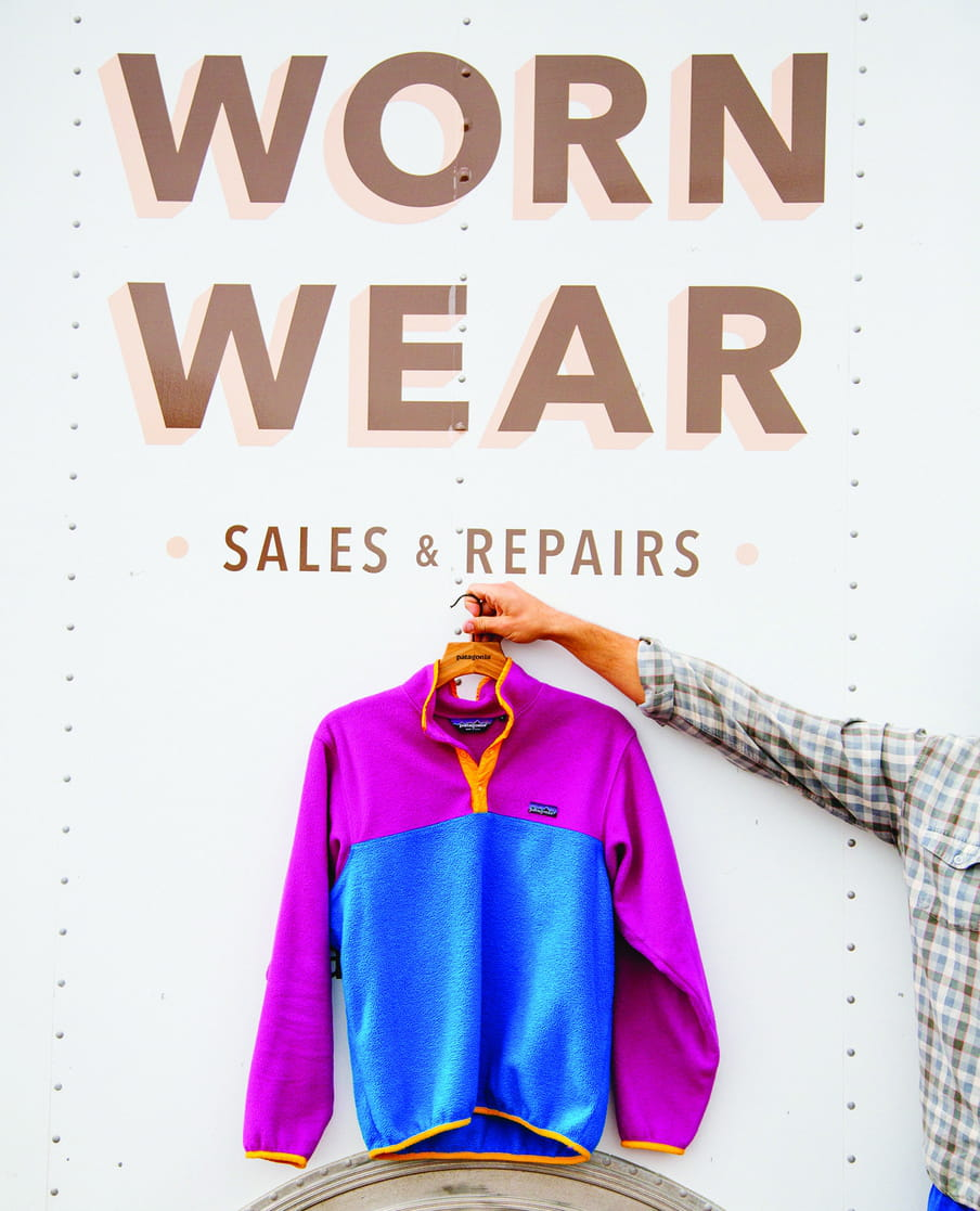 """Photo of an arm holding up a sweatshirt with the text on a wall above it stating: """"Work Wear Sales & Repair"""""""