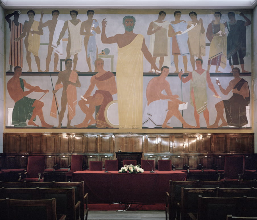 An empty ceremony hall that has been set up for a graduation ceremony. A red velvet cloth covers the table at the top of the room, overlooked by a Greek mural.