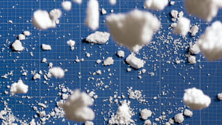 Photograph of white pieces of styrofoam looking like little clouds on a blue gridded background; a few of them are close up the camera, blurry clouds, while the rest lie in smaller pieces in the background, giving us a sense of dimension