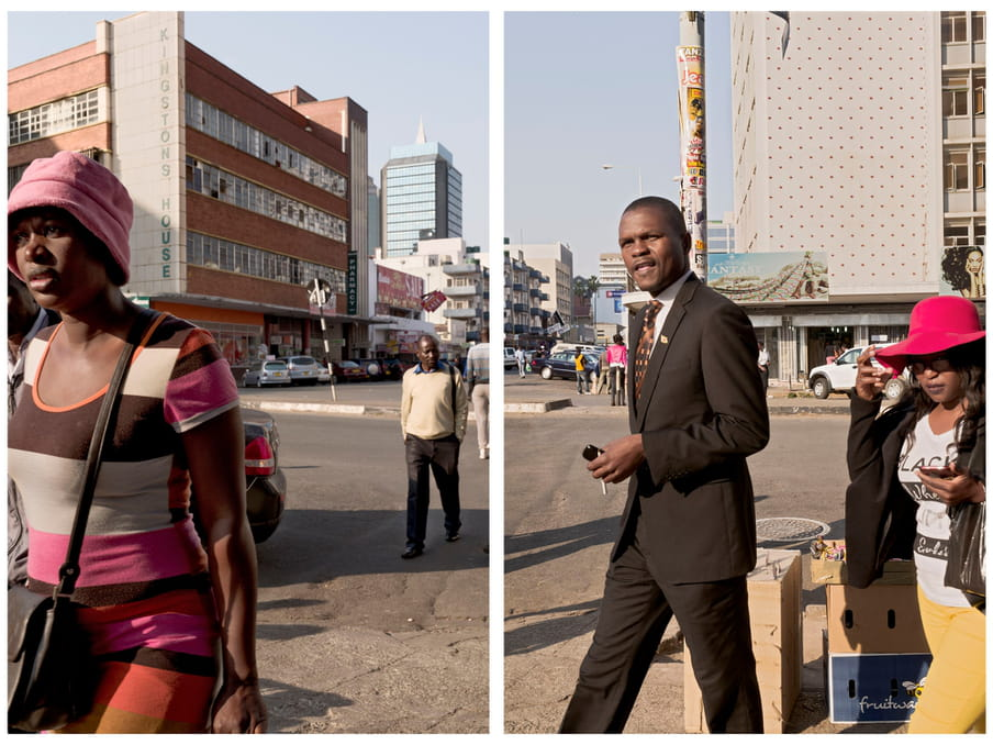 """An image of people walking across a street. In the front a woman wearing a colourful dress and a man in a suit. In the background a large building with a sign saying """"Kingstons House"""" and parked cars."""