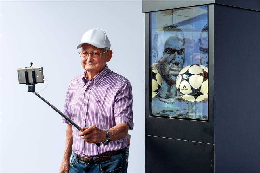 Photo of an older man in a white cap, with glasses, and a striped short-sleeved purple and white shirt tucked into blue jeans with a brown belt and newspaper folded into his back pocket, wearing a watch, holding a selfie stick up as he poses for a self-taken picture with his mobile phone in front of the Champion's League ball, encased in a glass and black cabinet behind him. There is a black and white drawing of a brooding footballer mirrored on two faces at the back of the cabinet.