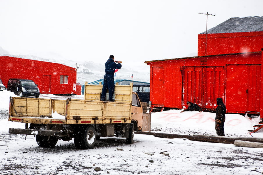 A man stands in the back of a beige pick up, taking a photograph of Te amo writing in the snow. Two other men are standing nearby.
