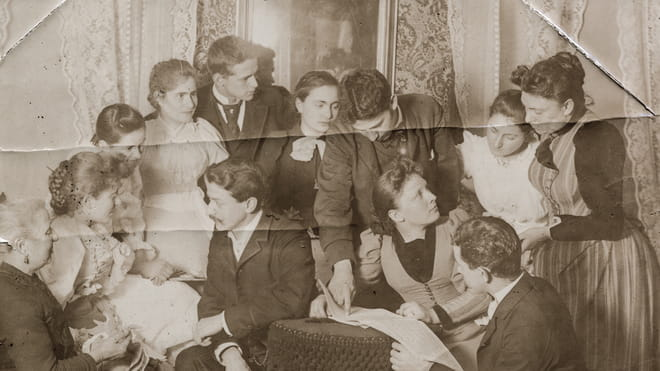 Old photo of people sitting together, damaged and folded