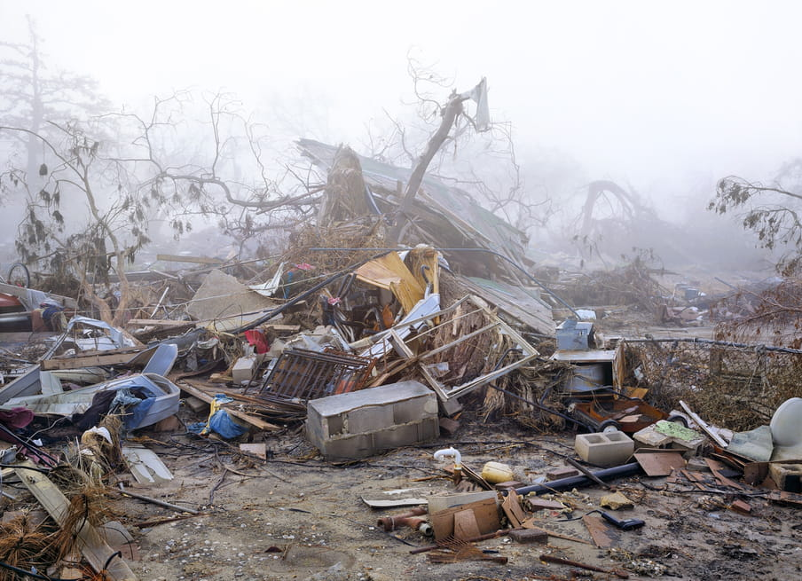 Photo of a destroyed house, not much of it left, against a misty background