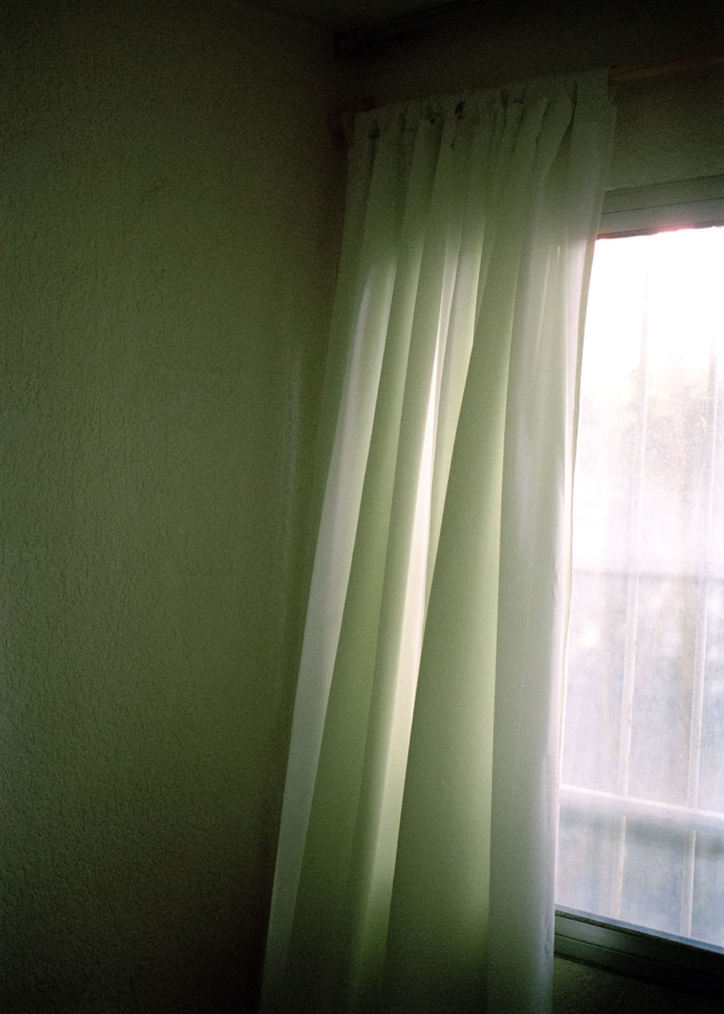 Photo of a closed window with flowing curtains and a wall beside it, with a greenish light around