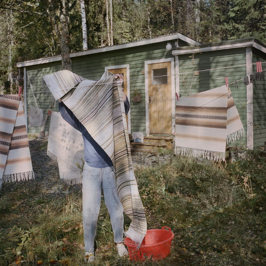 Photograph of a person hanging a rug on a clothesline that is already filled with three other rugs. An orange laundry basket sits besides them in the grass. In the background there is a small green wooden cabin and multiple trees.