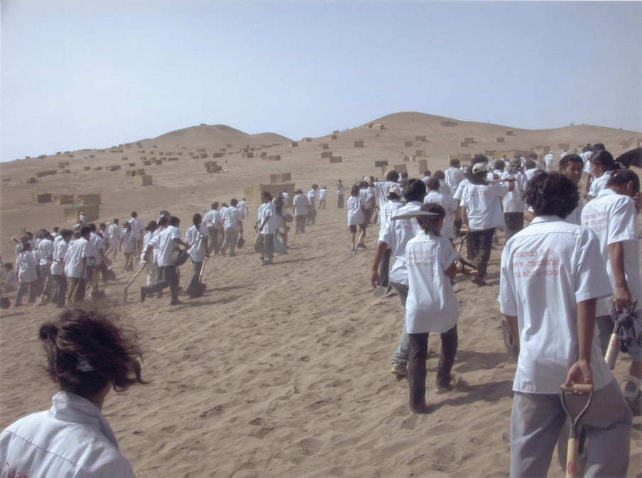 Landscape of a sandy desert, shot from the view of the backs of people in white shirts with messaging on the back, grey trousers, and shovels, climb up the dune. In the distance there are lots of sand blocks dotted all over the dune, which has peaks and troughs.