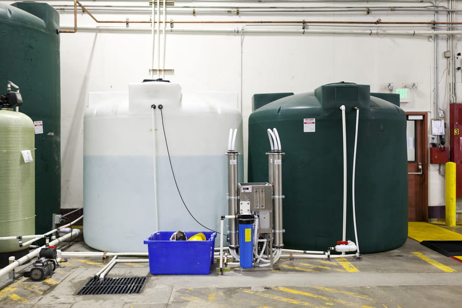 Two big tanks sit side by side on the floor with yellow markings - one is a white almost transprarent tank to the left, and is filled with water, the other is dark green and is filled with nutrients.