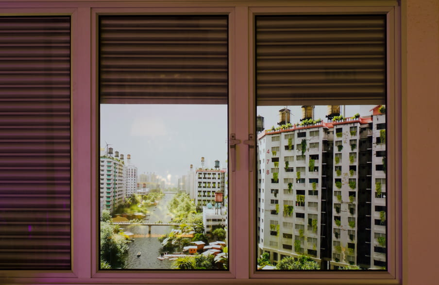 Photo of a fake window showing buildings with windmills on top of them and many, many plants