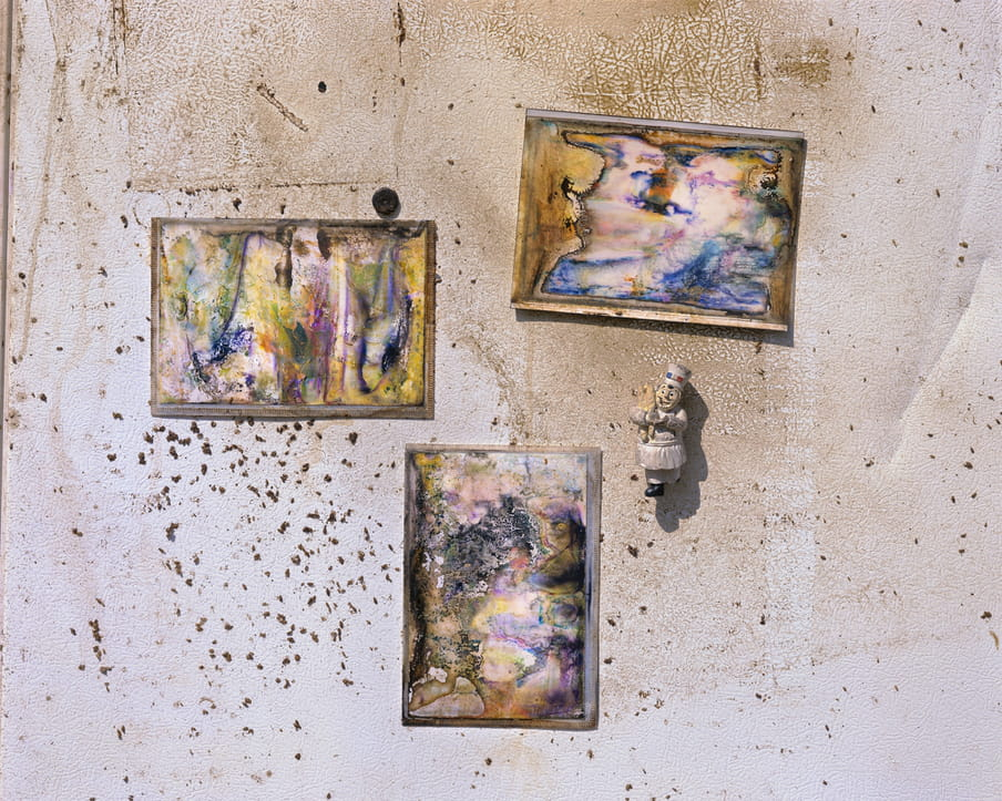 Photo of a wall with photographs with major water damage on it
