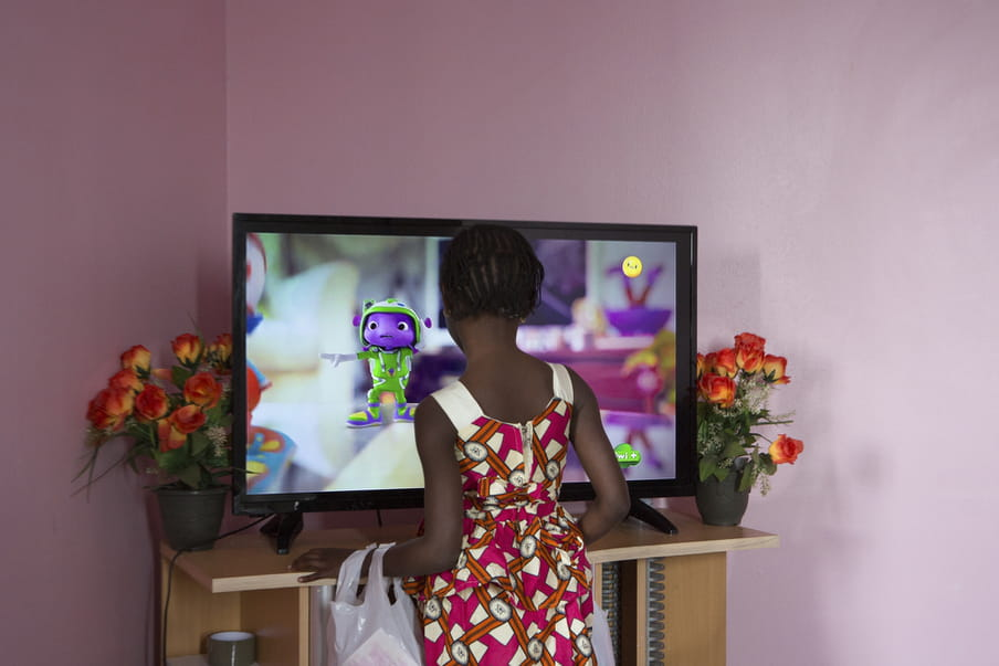 The back of a young black girl wearing a pink, white and orange patterned sleeveless summer dress, as she stands close to a television screen where the picture is blurred save for a purple 3D cartoon levitating figure in a green astronaut outfit, eyes out. The walls are lilac and there are two pots of orange flowers on either side of the TV, which is on a wooden stand.