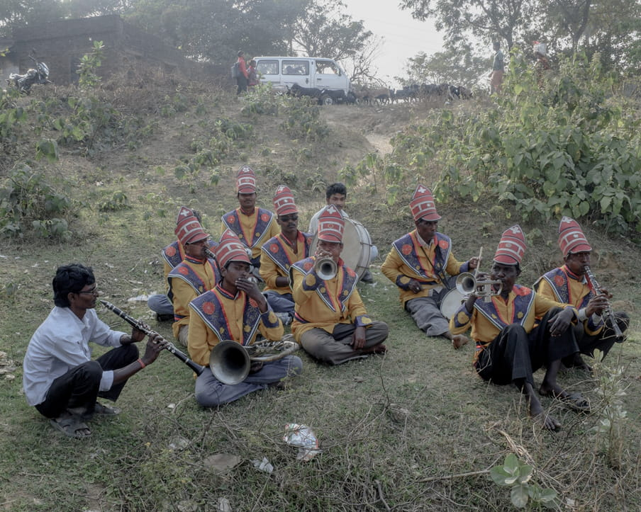 Ten Indian men sit cross-legged in a group on dry grass, dressed in a yellow, blue and pink uniform, with pink tall hats (only one plays a clarinet or flute in a simple shirt); they are part of a wind instruments ensemble, and are playing trumpets, or drums. Up the hill in the background we see a mini van.