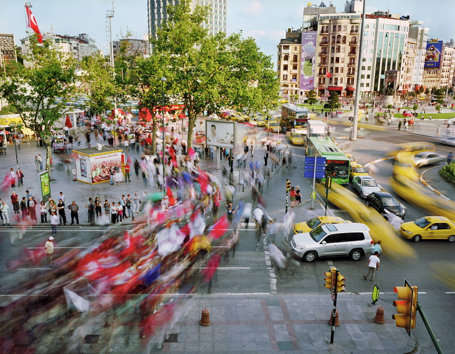 Photo of a busy street with a road trough it, yellow cabs and other cars on it. It's shot with a high shutter speed, so people are blurred