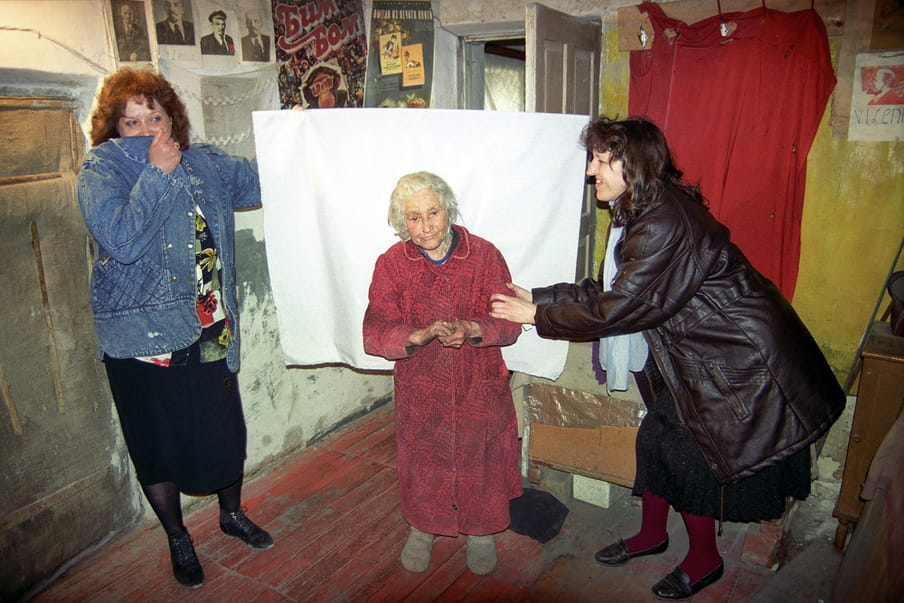 Central figure in a dressing gown, standing feebly due to her age, against a white sheet held up by two figures on either side, in a room with concrete walls and various posters on one side, and a red sheet hanging against a yellow wall on the other side