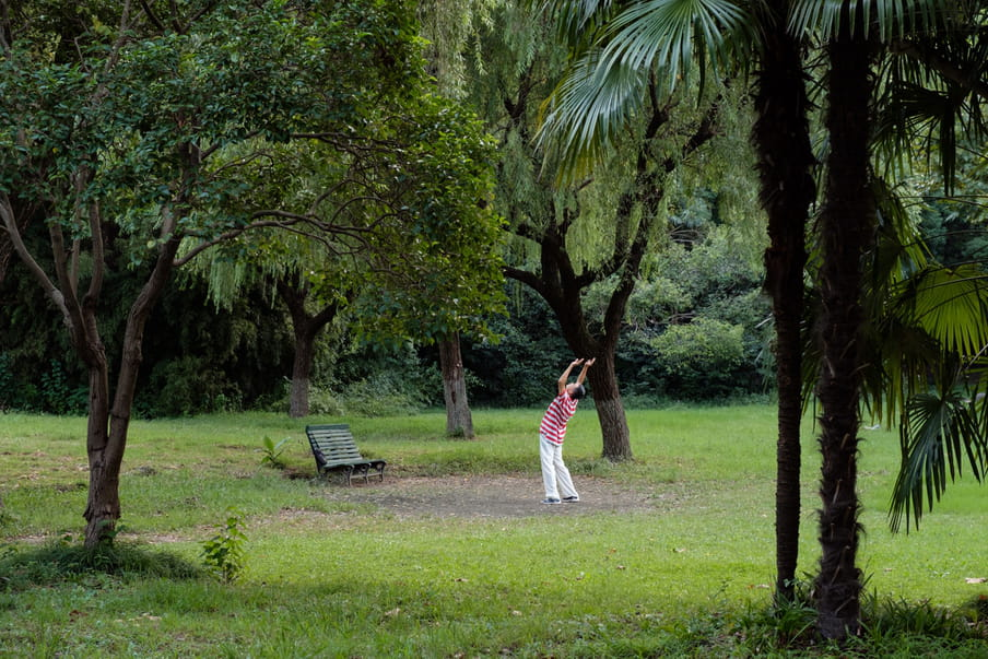 An old man stretching backwards in a green tropical park