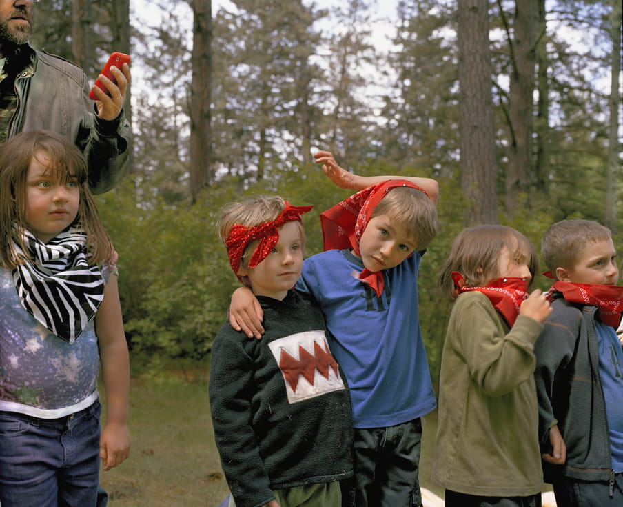 Photos of several kids standing in a row, with bandanas on their heads or arounds their necks. An adult in the back is checking his phone.
