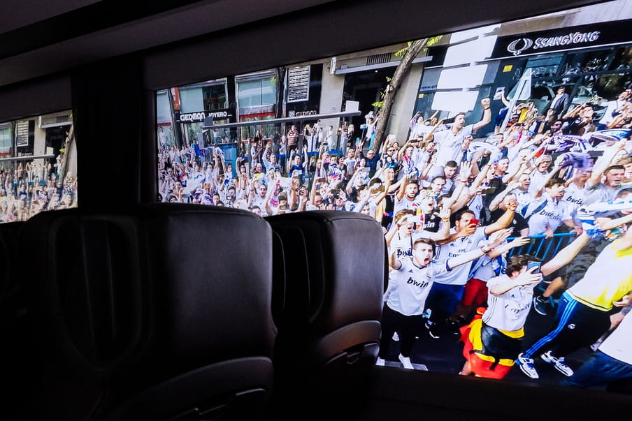 Photo from the inside of a coach. Outside fans of a football club are waving to the players.