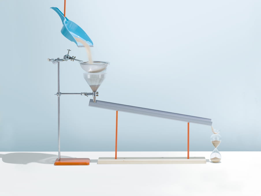 A blue dustpan is suspended from the top of this photo, a red tube pouring sand into it. The sand falls through a sieve and into a funnel, both attached to a metallic stand. The funnel links to a metal bar, pouring the sand into an hourglass on the right. The background is pastel blue, and the set-up casts shadows around.