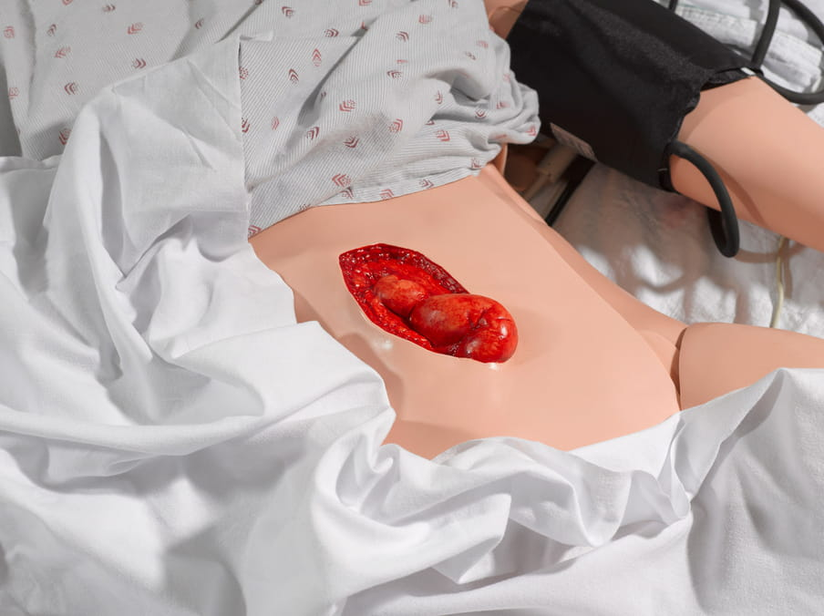 Close up photo of a fake operation on a plastic doll, belly exposed showing, fake organs.